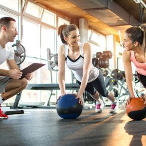 professor de educação física auxiliando duas alunas na academia
