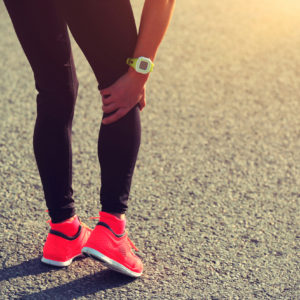 Imagem demonstra uma atleta com a mão na perna sentindo dores.