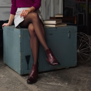 Female,Legs,In,Short,Skirt,And,Black,Pantyhose,Sitting,On